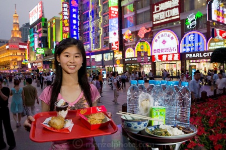 Chen Zhen, a university student, with her typical day's worth of food on Nanjing East Road in Shanghai, China. (From the book What I Eat: Around the World in 80 Diets.) The caloric value of her typical day's worth of food in June was 2600 kcals. She is 20 years of age; 5 feet, 5 inches tall and 106 pounds. Although she doesn't care for noodles or rice, a special rice roll is her favorite snack: black glutinous rice wrapped around youtiao (fried bread), pickled vegetables, mustard greens, and flosslike threads of dried pork. Zhen and her friends eat at KFC about three times a week, something they couldn't afford without the company's coupons. Meanwhile, her father and grandparents, who live in a tiny apartment in northeast Shanghai, go without meat during the week so they can afford to share a special meal with Zhen on her weekend visits. MODEL RELEASED.